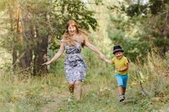 Avó nova com o neto que corre no parque no verão fotografia de stock royalty free