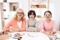 A avó nova, junto com seus netos, faz as caras com ajuda das escovas imagem de stock royalty free