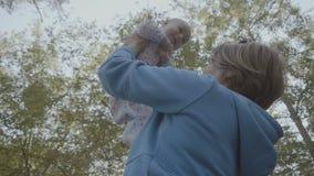 A avó nova levanta acima seu neto no movimento lento video estoque