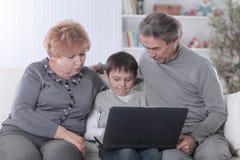 A avó, o avô e o neto olhando o portátil selecionam ao relaxar no sofá fotografia de stock