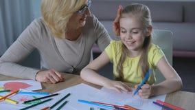 Avó que afaga a cabeça da neta, casa bonito da pintura da menina com lápis colorido video estoque