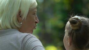 Avó que dá conselhos à neta bonito, relaxando no banco no parque filme