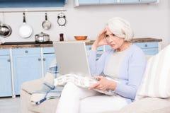 Avó que usa o laptop imagem de stock