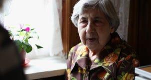 A avó senta-se perto da janela vídeos de arquivo