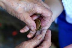 A avó toma o dinheiro da mão do seu neto imagem de stock