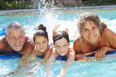 Avós com os netos no colchão de ar na piscina Fotos de Stock