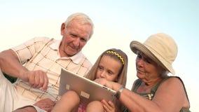 Avós e neta que jogam na tabuleta do PC video estoque