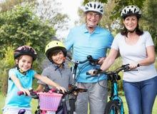 Avós e netos no passeio do ciclo no campo Imagens de Stock