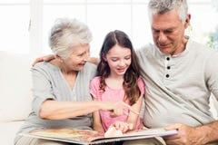 Avós felizes com a neta que lê um livro imagem de stock royalty free