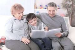 Avós loving com o neto que senta-se no sofá fotografia de stock