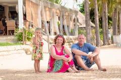 Avós que apreciam o dia com neta ao fundir bolhas de sabão na praia perto do mar fotos de stock royalty free