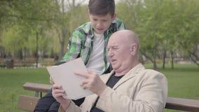 Av? bonito do retrato ascendente pr?ximo e neto ador?vel que sentam-se no parque no banco, anci?o que l? o livro para vídeos de arquivo
