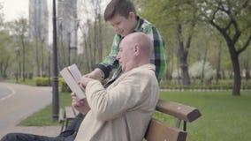 Av? bonito do retrato e neto ador?vel que sentam-se no parque no banco, anci?o que l? o livro para o menino filme