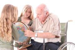 Avô da desvantagem que mostra a crianças o mundo Foto de Stock Royalty Free