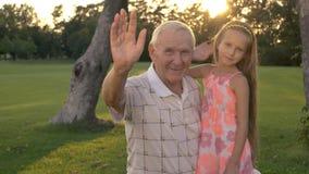 Avô e menina que acenam com mãos filme