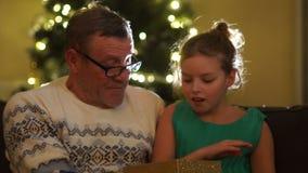 Avô e neta perto da árvore de Natal A menina abre o presente e exulta-o Presente do ` s do ano novo filme
