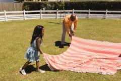 Avô e neta que colocam a cobertura do piquenique no quintal imagens de stock royalty free