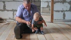 Avô e neto de trabalho do divertimento no canteiro de obras O avô ensina a seu neto o bebê martelar pregos filme