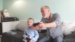 Avô e neto que jogam jogos de vídeo no computador com manche video estoque