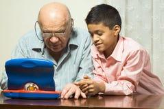 Avô e neto que olham um computador do brinquedo fotografia de stock royalty free