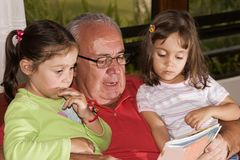 Avô e netos que lêem junto Imagens de Stock