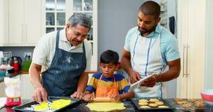 Avô e pai que ajudam ao menino a fazer as cookies 4k vídeos de arquivo
