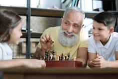 Avô engraçado que sorri ao jogar a xadrez com crianças Fotos de Stock Royalty Free