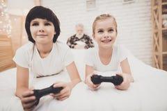 Avô, neto e neta em casa As crianças estão jogando jogos de vídeo quando o vovô dormir fotografia de stock royalty free