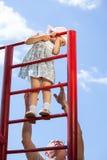 Avô apoiando uma escalada da neta escadas Fotos de Stock
