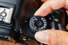 Av dial mode on dslr camera with fingers on the dial.  royalty free stock images