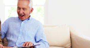 Avô e neta que olham um livro junto vídeos de arquivo
