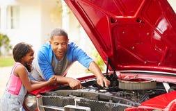 Avô e neta que trabalham no carro restaurado fotografia de stock