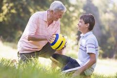 Avô e neto em um parque com uma esfera Imagens de Stock