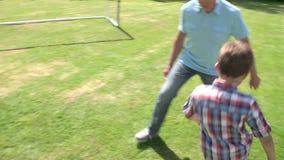 Avô e neto que jogam o futebol no jardim em casa filme
