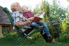 Av? e neto que leem um livro fora Est?rias boas imagem de stock royalty free