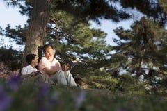 Avô e neto que relaxam sob uma árvore e livros de leitura em um parque na primavera, Pequim fotos de stock royalty free