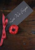 Av fruktan att vi glömmer, återanvände röda Poppy Lapel Pin Badge på mörker trä - lodlinje arkivfoto