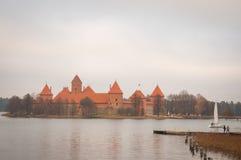 By av Karaites, Litauen, Europa Litauisk gränsmärke i sen höst Sikten till pir- och yachtseglingen på sjön nära Trakai Arkivbilder