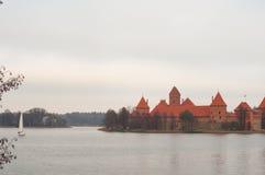 By av Karaites, Litauen, Europa Litauisk gränsmärke i sen höst Yachtsegling på sjön nära den Trakai halvöslotten Mus Royaltyfria Foton