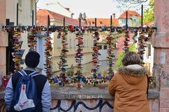 10 av Maj, 2017, redaktörs- foto av staketet på bron med lås och två turister Kampa, Prague, Tjeckien royaltyfria bilder