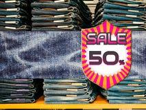 50% av på blå grov bomullstvilljeans shoppar in bakgrund Arkivfoton
