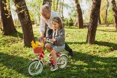 Avô que ajuda à menina com bicicleta imagens de stock royalty free