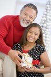 Avô que dá a sua neta um presente Fotografia de Stock Royalty Free