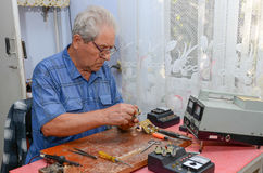 Avô que trabalha com um ferro de solda Imagens de Stock Royalty Free