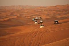 Av-väg affärsföretag med SUV som kör i arabisk öken på solnedgången Offroad medel som slår till och med sanddyn i den Dubai öknen arkivbild