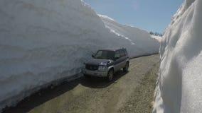 Av-väg auto Mitsubishi Pajero iO som kör på höglandvägen i snötunnelen som omges av höga snödrivor arkivfilmer