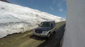 Av-väg bil Mitsubishi Pajero iO som kör på bergvägen i snötunnelen som omges av höga snödrivor stock video