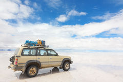 Av-väg bil på den reflekterade yttersidan av sjön Salar de Uyuni i Bolivia Arkivbilder