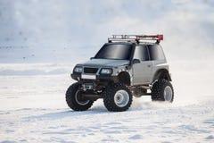 Av-vägen bilen med stora hjul kör på snö Arkivfoto