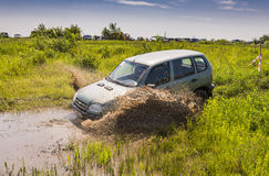 Av-vägen medelmärket NIVA- Chevrolet övervinner en grop av gyttja Arkivbild